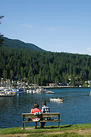 Couple looking at boats moored with the trees of the Cove forest in the background. Deep Cove, Burrard Inlet, Vancouver, British Columbia, Canada.