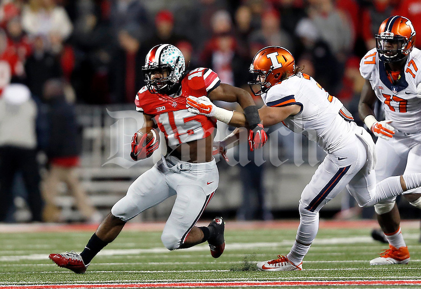 Ohio State Buckeyes running back Ezekiel Elliott (15) tries to elude Illinois Fighting Illini defensive back Taylor Barton (3) in the third quarter of the NCAA football game at Ohio Stadium on Saturday, November 1, 2014. (Columbus Dispatch photo by Jonathan Quilter)