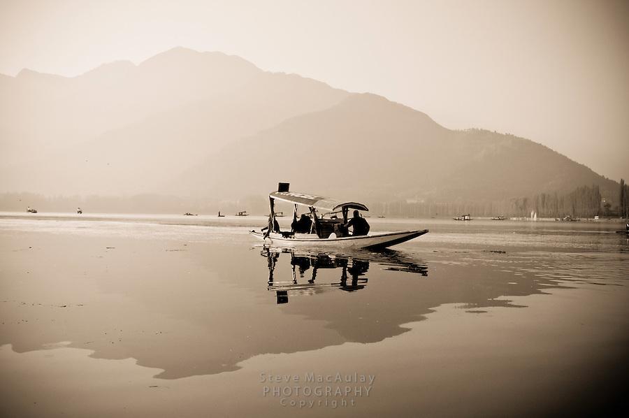 Traditional Kashmiri shikara on Dal Lake at sunrise, Srinagar, Kashmir, India.