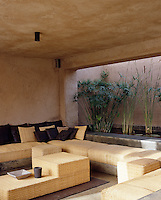 The pond and custom designed wicker furniture make this loggia a cool and calm respite from the hot sun