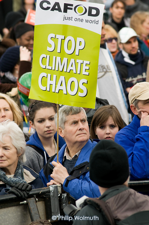 Man with a CAFOD climate change placard at a TUC rally in Hyde Park a few days before a London G20 meeting.