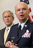 Langley, VA - May 31, 2006 -- United States President George W. Bush, left, looks on as his new Central Intelligence Agency (CIA) Director General Michael Hayden speaks during a ceremonial swearing in at CIA headquarters in Langley, Virginia Wednesday 31 May 2006. Hayden, the former head of the super-secret National Security Agency (NSA), was officially sworn-in by National Intelligence Director John Negroponte in a closed ceremony.<br /> Credit: Matthew Cavanaugh-Pool via CNP