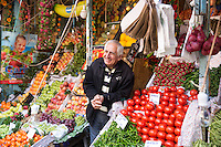 Turkish shopkeeper selling fresh vegetables on sale at food and spice market in Kadikoy district Asian side of Istanbul, Turkey