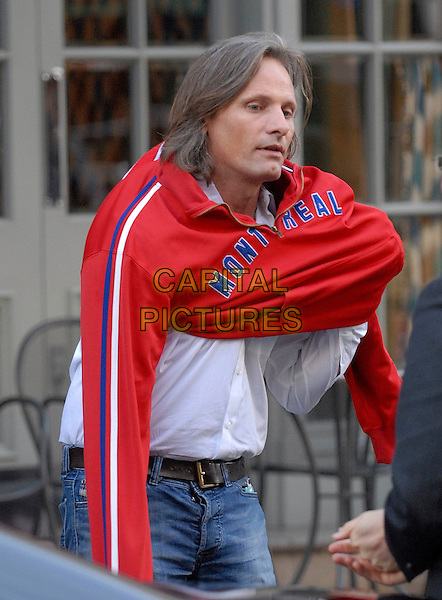 VIGGO MORTENSEN.Seen leaving the Charlotte Street Hotel,.London, England, UK, .October 18th 2009..half length white shirt putting on red jumper top montreal slogan .CAP/IA.©Ian Allis/Capital Pictures.