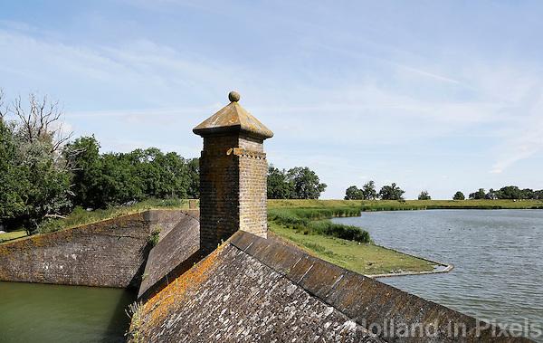 Muiden. Holle Sluisbeer bij het Muiderslot. De vesting Muiden maakte al vanaf de zeventiende eeuw deel uit van de toenmalige Hollandse Waterlinie. Oorspronkelijke doel van het fort was het afsluiten van de doorgangen via de Zeedijk (noord) en de Naardertrekvaart (zuid) . In 1851 werd bij het Muiderslot een unieke holle sluisbeer gebouwd voor het in- en uitlaten van water tijdens de inundaties. Met een ingenieus systeem konden de sluiskokers van binnenuit bediend worden en vanuit de geweerschietsleuven in de beer werd de gracht onder schot gehouden.