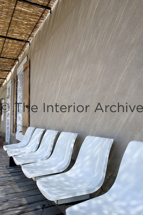 A row of white chairs runs along the wall of the house in the shade of the awning on the covered terrace