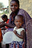 Kabinga Village, Zambia. Young African woman with baby with tears in her eyes holding an inflated condom balloon.
