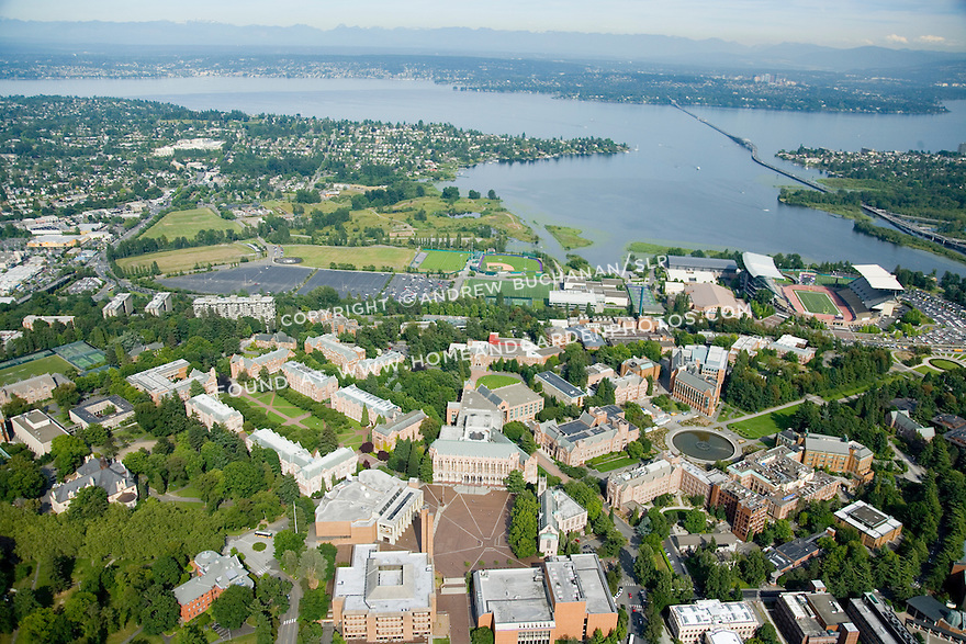Late afternoon summer aerial photo looking east towards the Cascade Mountains and showing the University of Washington's main Seattle campus, the Evergreen point Floating Bridge carrying Highway 520 across Lake Washington, and the eastside suburbs of Seattle, WA beyond.