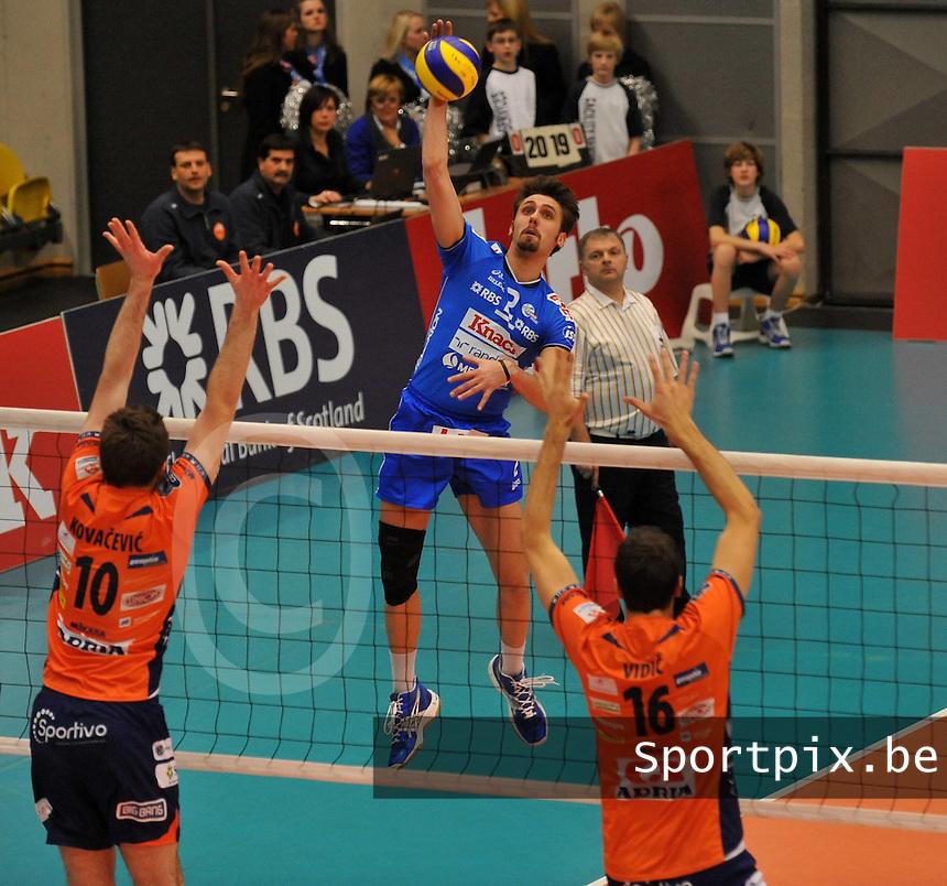 Knack Roeselare - ACH Volley Ljubljana : Hendrik Tuerlinckx met de smash tussen de blokkende Uros Kovacevic (links) en Matej Vidic.foto VDB / BART VANDENBROUCKE