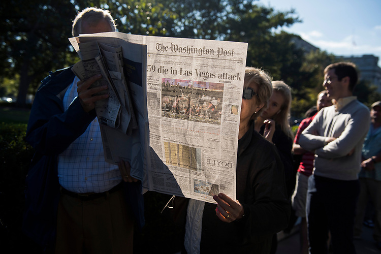 UNITED STATES - OCTOBER 03: People read the newspaper featuring coverage of the Las Vegas shooting outside the Supreme Court on October 3, 2017. The Court is hearing a case on possible partisan gerrymandering by state legislatures. (Photo By Tom Williams/CQ Roll Call)