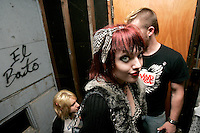 Concert-goers move from the basement to the garage for a cigarette break during a punk concert at the White House in Woodstock, Illinois.  The White House was a small suburban residential home rented by a group of 20-somethings in Woodstock, Illinois, a distant northwestern suburb of Chicago.  For about a year, the renters of the house staged punk-rock concerts in the house's small basement, without the approval of the neighborhood, local government, or police.  .
