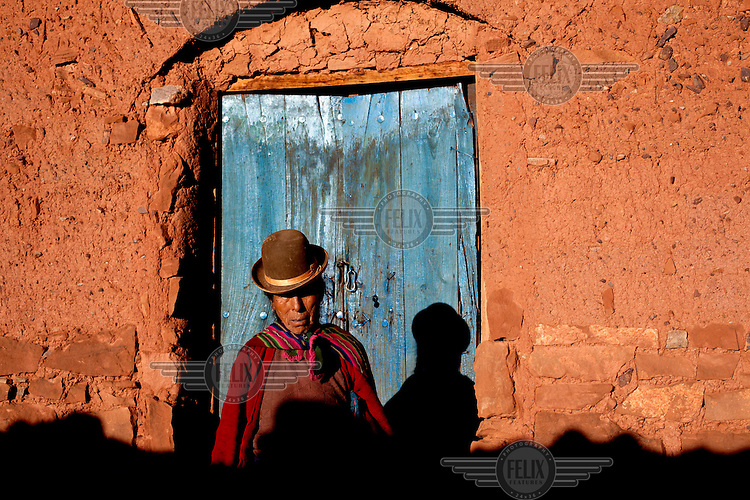 A woman stands in front of a blue door in Macha. <br /> <br /> The people of Macha and surrounding communities carry on the pre-Columbian tradition of ritual fighting. The communities gather on the plaza of Macha to fight and dance in competition with each other. The blood that is spilled is an offering to Mother Earth. In return, the people ask for rain and a good harvest. This ritual is called tinku or fiesta de la cruz since the cross is also engaged in the festivities. The cross is dressed up, given offerings and brought from communities around Macha to the church in town. This syncretic festival melds pagan, pre-christian rituals with Catholic practice. /Felix Features