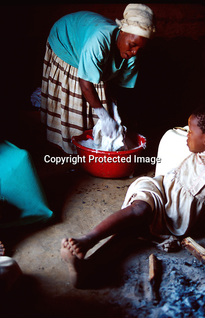 dipprur00011 People Rural Margarett Shenge, 37, is infected by the Aids virus. She lives in Nqbeni a rural area in Natal, South Africa with four children. Two of the children are also infected by Hiv; rural; woman washing, boy next to fireplace.©Per-Anders Pettersson/iAfrika Photos
