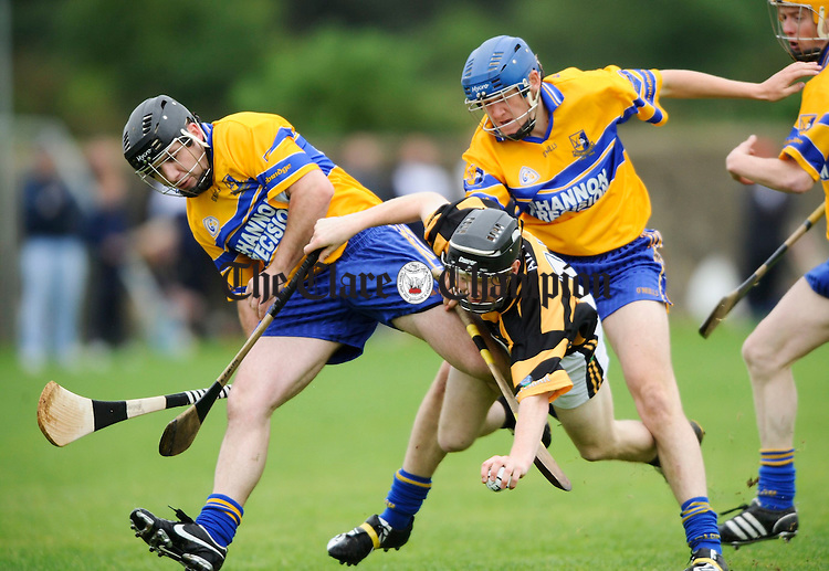 Tubber's Blaine Earley goes down under pressure from Sixmilebridge's Christy Griffin and ???? during their championship game at Tulla. Photograph by John Kelly.