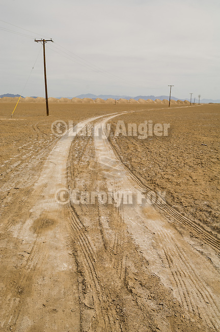 Dirt road, piles, power lines on the lake playa of Bristol Lake, Calif.