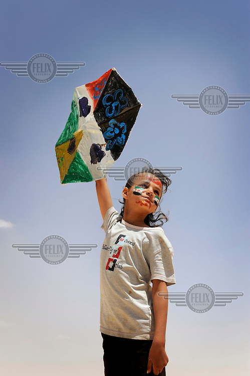 Syrian refugee Sherine holds up a kite which she made herself and has her personal message of peace for her country wtitten on it. Sherine used her favorite colours on her kite and drew flowers and hearts around it. She has been a refugee for seven months now and says ,'These colours and flowers remind me of my home.' /Felix Features