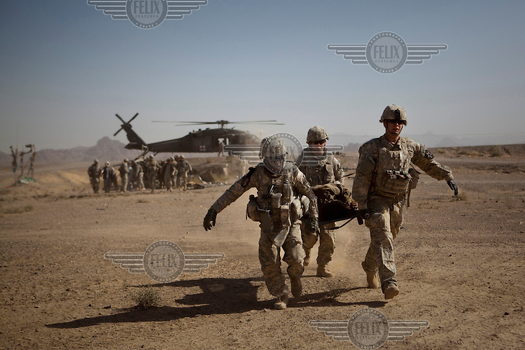 US Army soldiers carry wounded civilians onto Charlie Company, Sixth Battalion, 101st Aviation Regiment medevac helicopters after their vehicle hit an IED (improvised exposive device) near Kandahar.