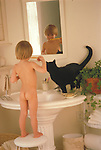 nude young boy standing on stool brushes teeth in bathroom