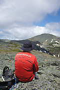 A hiker enjoys the view of Mount Washington from the summit of Boott Spur Mountain during the summer months. Located in the White Mountains, New Hampshire USA