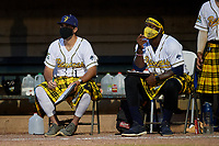 Savannah Bananas coaches Corey Pye (left) and Errick Fox (right) sit outside the dugout to practice social distancing, while wearing a mask, during a Collegiate Summer League game against the Macon Bacon on July 15, 2020 at Grayson Stadium in Savannah, Georgia.  (Mike Janes/Four Seam Images)
