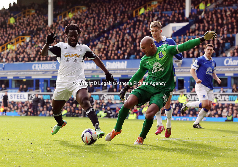 Pictured L-R: Wilfried Bony of Swansea has his shot stopped by Everton goalkeeper Tim Howard. Saturday 22 March 2014<br />