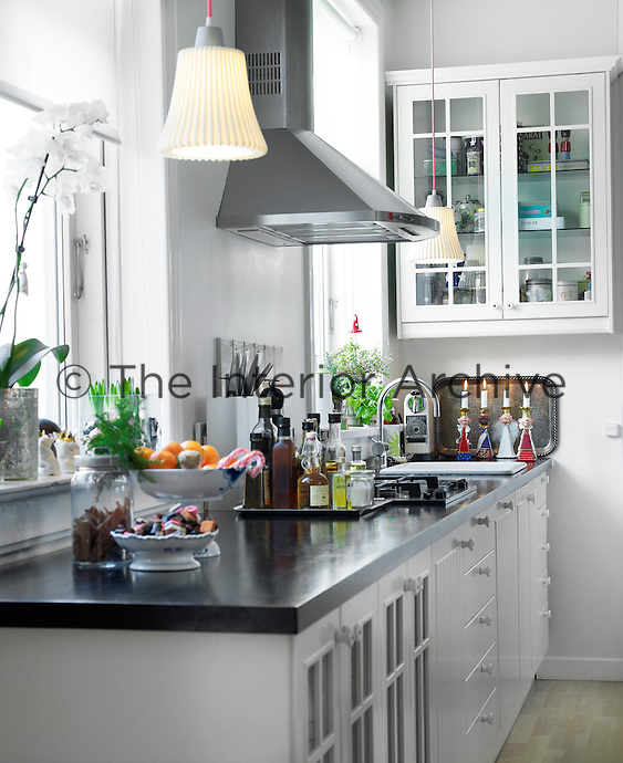 Christmas candles burn brightly at the end of the sturdy black worktop in this simple kitchen