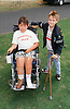 Young boy with disability; who is electric wheelchair user; with friend holding walking sticks,