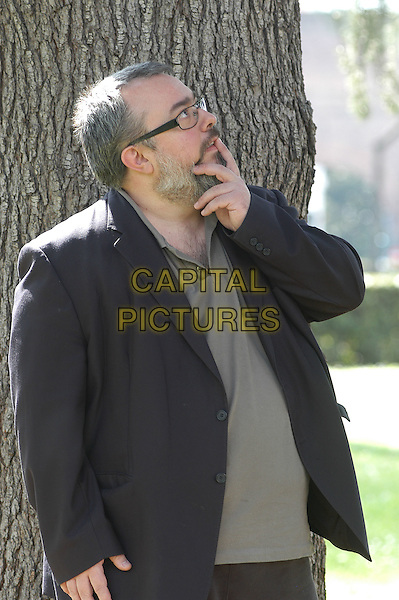 "ALEX DE LA IGLESIA.Photocall for ""The Oxford Murders"", Rome, Italy..April 2nd, 2008 .half length blue jacket grey gray top hand profile pensive thinking looking up  beard facial hair glasses .CAP/CAV.©Luca Cavallari/Capital Pictures."