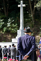 An old man watches dignitaries and aying wreaths of poppies at the Cross of Sacrifice Remembrance Sunday ceremony at the Hodogaya, Commonwealth War Graves Cemetery in Hodogaya, Yokohama, Kanagawa, Japan. Sunday November 12th 2017. The Hodagaya Cemetery holds the remains of more than 1500 servicemen and women, from the Commonwealth but also from Holland and the United States, who died as prisoners of war or during the Allied occupation of Japan. Each year officials from the British and Commonwealth embassies, the British Legion and the British Chamber of Commerce honour the dead at a ceremony in this beautiful cemetery.