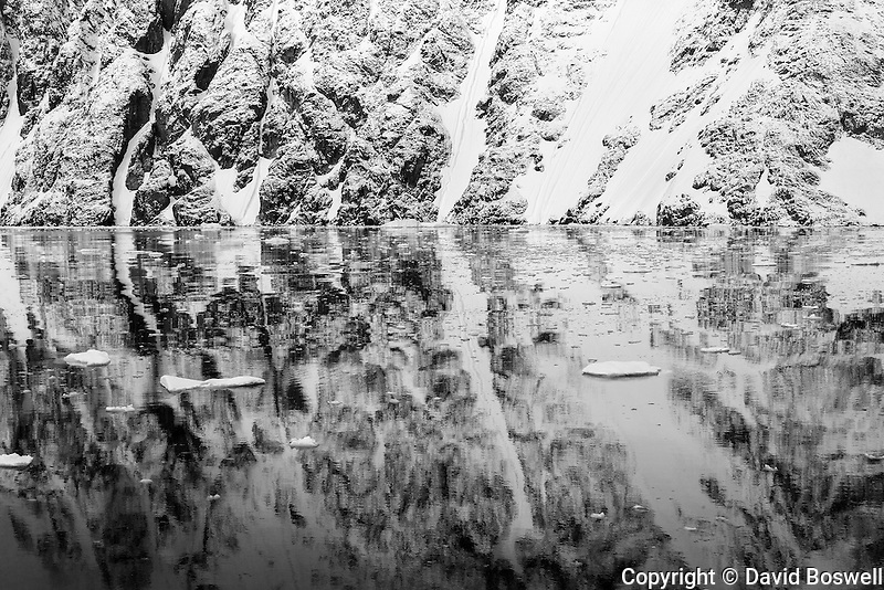 The surrounding cliffs and ice provide abstract reflections off the calm waters of the Lemaire Channel, Antarctica.