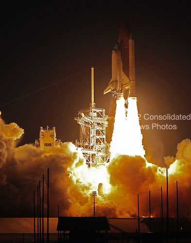 Cape Canaveral, FL - March 15, 2009 - Space shuttle Discovery roars off Launch Pad 39A on the STS-119 mission atop twin towers of fire that light up the sky after sunset at NASA's Kennedy Space Center in Florida. Liftoff was on time at 7:43 p.m. EDT, Sunday, March 15, 2009. The STS-119 mission is the 28th to the International Space Station and the 125th space shuttle flight. Discovery will deliver the final pair of power-generating solar array wings and the S6 truss segment. Installation of S6 will signal the station's readiness to house a six-member crew for conducting increased science. Liftoff is scheduled for 7:43 p.m. EDT. .Credit: Scott Andrews - NASA via CNP