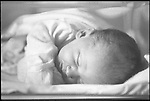 newborn baby girl sleeping in hospital bassinet