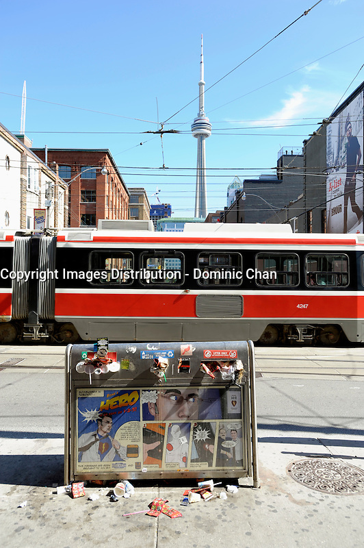 Toronto (on) CANADA, July 4, 2009  Toronto Garbage Strike - full garbage can on Queen Street West with CN Tower and TTC  street car in the background.