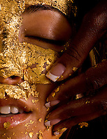 Audrey Armah gives a 24K gold facial to Vanya Georgieva.  They apply gold leaf to the face to brighten the skin for beauty.