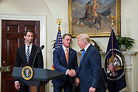 "United States President Donald J. Trump shakes hands with US Senator David Perdue (Republican of Georgia), during an announcement on the introduction of the Reforming American Immigration for a Strong Economy (RAISE) Act in the Roosevelt Room at the White House in Washington, D.C., U.S., on Wednesday, August 2, 2017. The act aims to overhaul U.S. immigration by moving towards a ""merit-based"" system.  Pictured at left is US Senator Tom Cotton (Republican of Arkansas). Photo Credit: Zach Gibson/CNP/AdMedia"