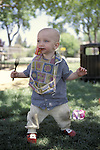 Berkeley, CA Baby boy eleven months balancing in standing position while holding dangerous fork and finishing off a box of raisins  MR