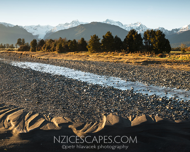 Farmland with creek under Aoraki Mount Cook and Mount Tasman of Southern Alps at sunrise, Westland Tai Poutini National Park, UNESCO World Heritage Area, West Coast, New Zealand, NZ