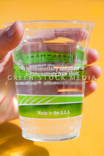 Close-up of person holding a Fabri-Kal's Greenware cold drink cup full of water. The cup reads 'This environmentally sustainable up is made entirely from plants'. Made in American from NatureWorks Ingeo biopolymer, a resin derived entirely from plants. The cups are used for drinking water for customers at the outside tables of the Coast Cafe in Bolinas, California, USA