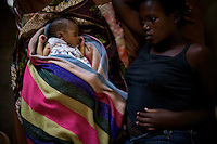 """Just a few days from a fragile cease fire, a woman lies next to her newborn baby  in the Rurthsuru hospital in a rebel controlled area on monday November 3 2008 70 kms from North Kivu's capital Goma, in war torn Eastern Democratic Republic of Congo.///..Today a UN convoy has arrived in rebel-held areas in eastern Democratic the Republic of Congo, carrying aid for people affected by recent fighting..The convoy brought medicine to the town of Rutshuru. Food is expected later..But aid workers found that refugee camps that had held tens of thousands are now virtually empty. It is believed many people left fearing attacks..Last week rebels led by Laurent Nkunda routed the Congolese army near Goma, the capital of North Kivu province..A fragile ceasefire is now in place, and Gen Nkunda has said he will guarantee """"humanitarian corridors"""" for the convoy through rebel lines."""