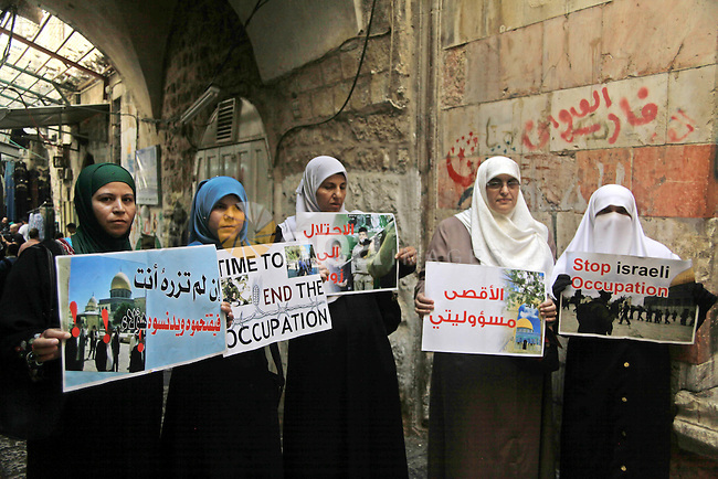 Palestinian women from the so-called Murabitat group carry placards and shout slogans in front of Israeli security forces during a protest against Jewish groups visiting the Al-Aqsa mosque compound and against preventing them from entering the shrine on September 30, 2015. Photo by Mahfouz Abu Turk
