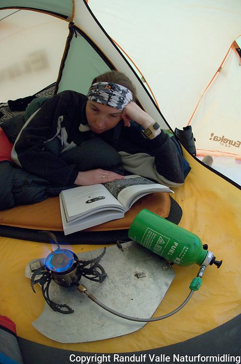 Jente ligger i telt og leser bok foran primusen ---- Girl in tent reading book in front of the stove