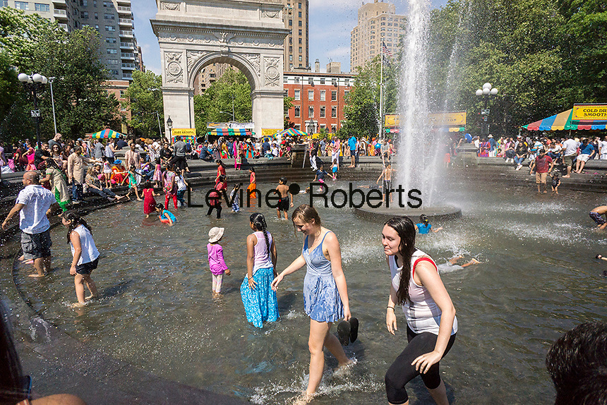 New Yorkers and visitors enjoy the fountain in Washington Square Park in Greenwich Village in New York on Saturday, June 10, 2017. Although only going into the 80's blistering heat is expected during the next three days giving the city a heat wave. ( © Richard B. Levine)
