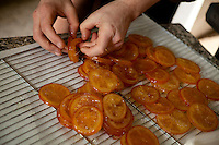 Chocolatier Patrice Arbona separates slices of orange in syrup in his shop 'Entre Mes Chocolats', Vence, France, 10 February 2011