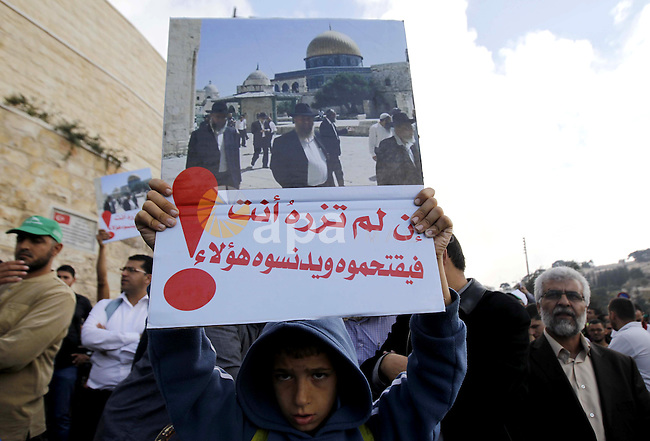 Palestinians shout slogans during a rally near the entrance of al-Aqsa mosque compound to protest after authorities restricted access to the esplanade on October 15, 2014 outside Jerusalem's Old City. For the second time in a week, authorities allowed only Palestinians aged over 50 to enter. Four Palestinians were arrested and three police were injured during clashes that followed the protest, police spokeswoman Luba Samri said. Photo by Muammar Awad