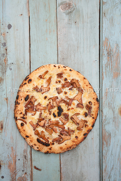 Fresh baked whole pizza with blistered crust, chanterelle mushrooms, and mozzarella cheese on an olive oil base. Overhead view, on a teal painted wood surface.
