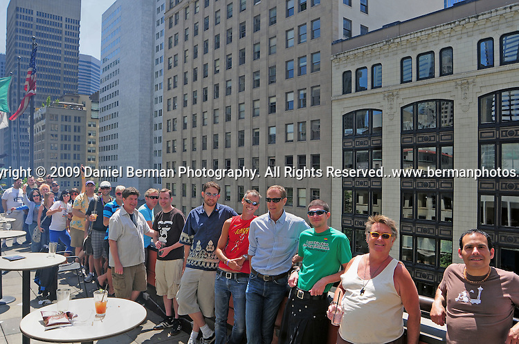 Visitors to the Red Lion Hotel on Fifth Avenue in Seattle take in an overhead view of the Pride Parade from the rooftop lounge Sunday June 28, 2009.