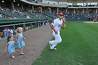 Shortstop Hector Lorenzana (5) of the Greenville Drive runs onto the field with two small fan in a game against the Greensboro Grasshoppers on Thursday, August 27, 2015, at Fluor Field at the West End in Greenville, South Carolina. Greenville won, 10-2. (Tom Priddy/Four Seam Images)