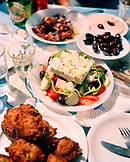 GREECE, Patmos, Diakofti, Dodecanese Island, a table of food including olives and a Greek salad at the Diakofti Taverna