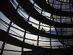Visitors walking in the Norman Foster-designed glass cupola on the roof of the Reichstag, the German Parliament building in the city centre adjacent to where the Berlin Wall ran. The Wall divided Berlin and Germany for 29 years from 1961. A popular uprising took place in East Germany in 1989 and lead to the end of the Cold War and the re-unification of Germany after which Berlin became the nation's capital city once more.