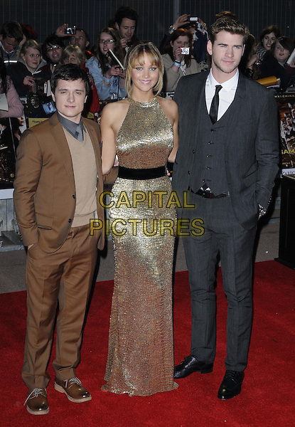 Josh Hutcherson, Jennifer Lawrence & Liam Hemsworth.European Premiere of 'The Hunger Games' at Cineworld at the O2 Arena, London, England..March 14th 2012.full length brown suit jumper sweater gold sleeveless dress black belt grey gray suit waistcoat .CAP/CAN.©Can Nguyen/Capital Pictures.